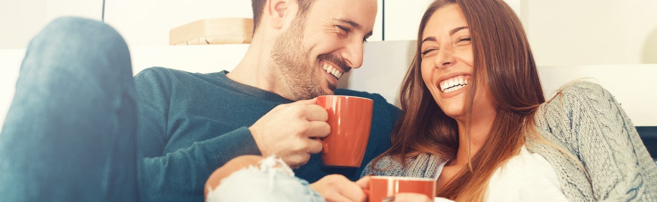 Man and woman laughing over a cup of coffee