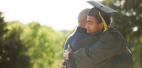 Young student graduating hugging family member